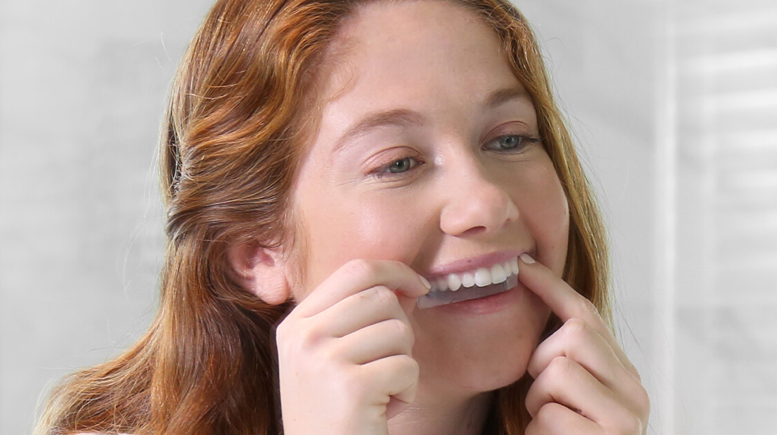 Red haired girl applying Crest Whitestrips with white background | Crest White Smile