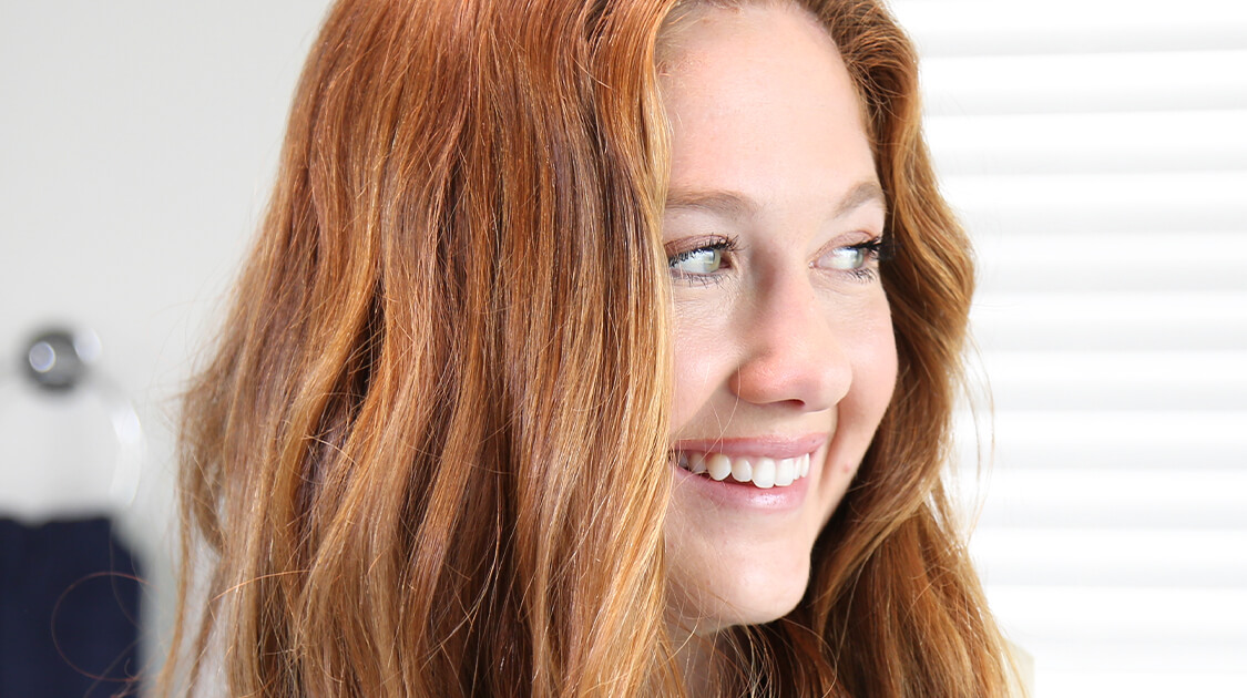 Red haired girl smiling with white teeth in the bathroom | Crest White Smile